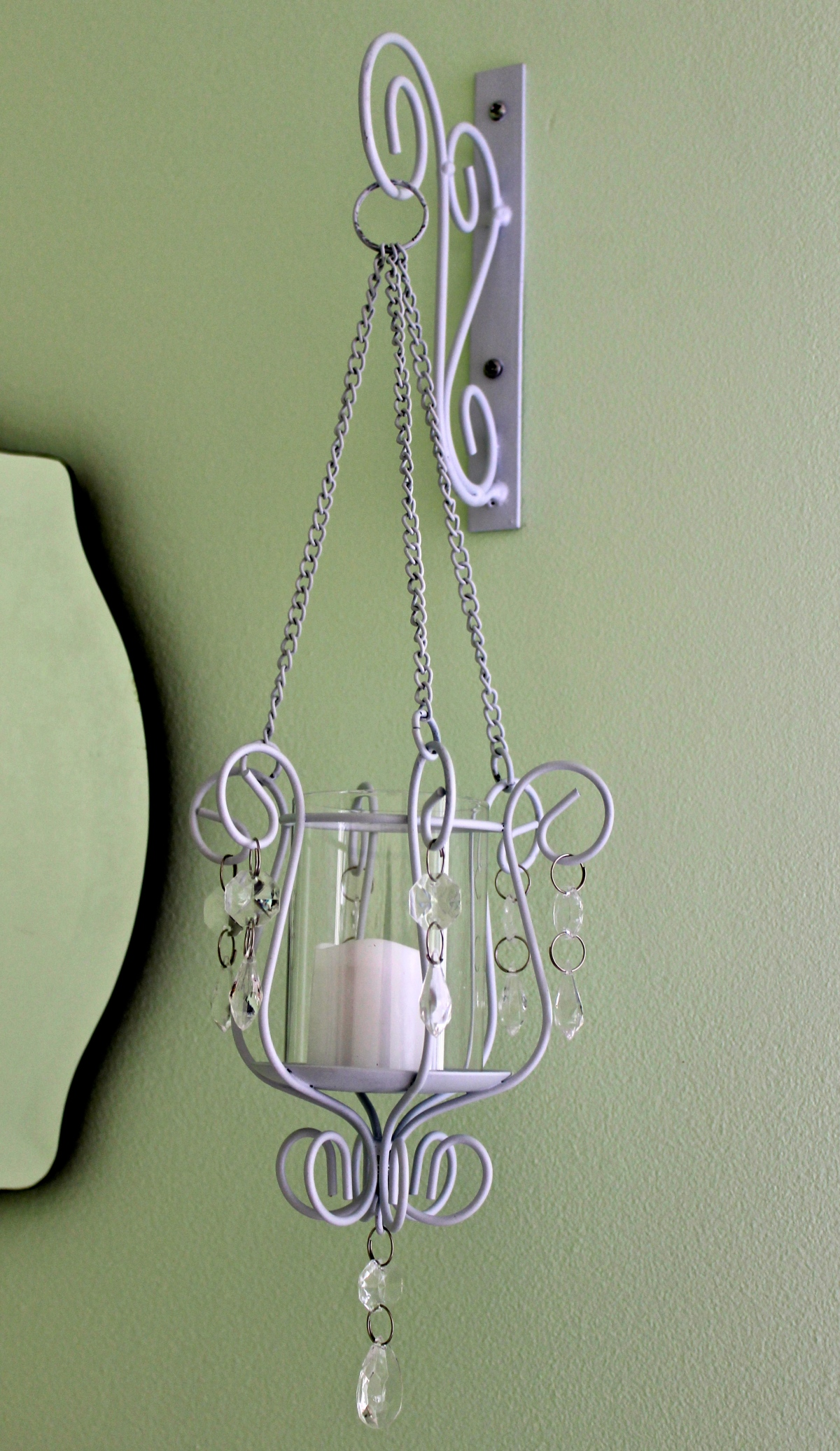 Sconces add a unique accent to the vintage mirror. Photo by Alexa